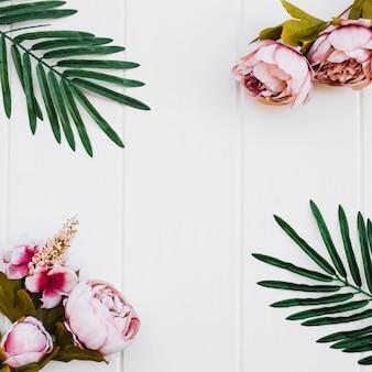 Róże i rośliny na białym drewnianym tle