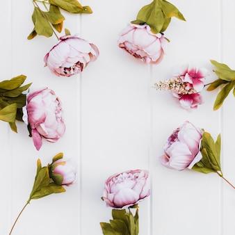 Róże umieszczone w okręgu na białym tle drewna
