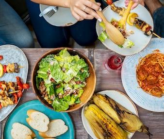 Różni ludzie jedzą jedzenie razem