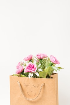 Różowa wiązka kwiatów goździka wewnątrz brązowej papierowej torby