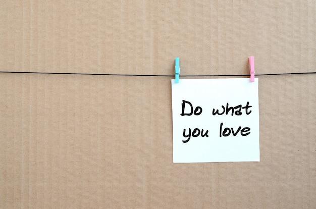 Rób to co kochasz. uwaga jest zapisana na białej naklejce, która wisi na spinaczu na linie na tle brązowej tektury