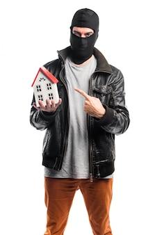 Robber trzyma mały dom