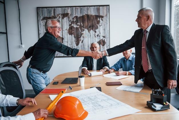 Robi uścisk dłoni. starszy zespół architektów biznesmenów w podeszłym wieku spotyka się w biurze.