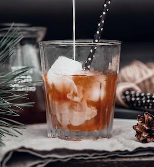Robiąc zimną latte strużkę mleka wlewa się do czarnej kawy w przezroczystym szklanym kubku na...