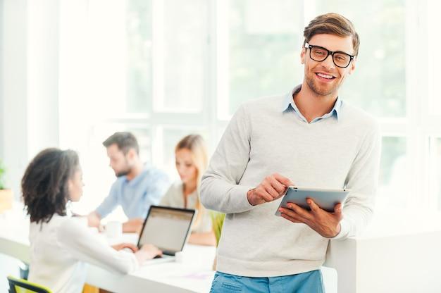 Robić interesy z uśmiechem. szczęśliwy młody człowiek trzymający cyfrowy tablet i patrzący na kamerę, podczas gdy jego koledzy pracują w tle
