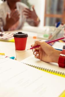Robić notatki. sylwetka ciemnoskórego nauczyciela aktywnie gestykulującego podczas wyjaśniania nowego materiału