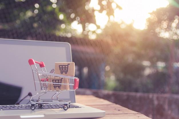 Robić zakupy online pojęcie - pakuneczek lub papierowi kartony z wózek na zakupy logem w tramwaju na laptop klawiaturze. usługa zakupów w internecie. oferuje dostawę do domu.