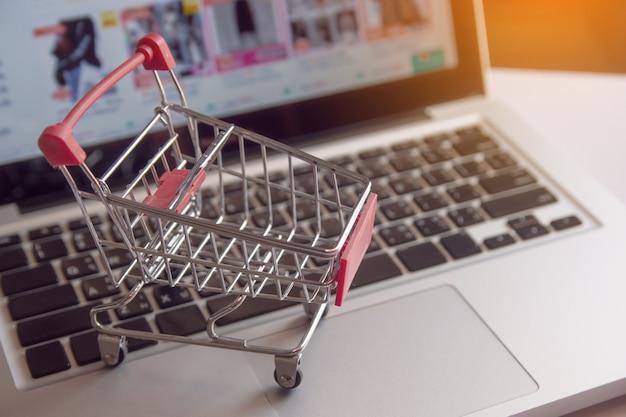 Robić zakupy online pojęcie - wózek na zakupy lub tramwaj na laptop klawiaturze. usługa zakupów w internecie. z miejsca na kopię