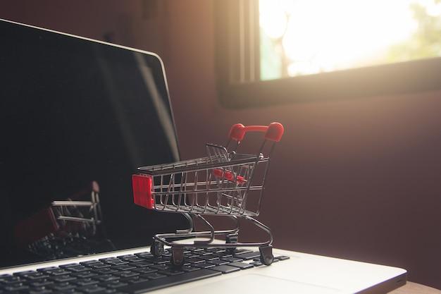 Robić zakupy online pojęcie - wózek na zakupy lub tramwaj na laptop klawiaturze. usługa zakupów w internecie.