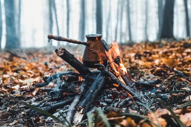 Robię kawę na stosie. przygotuj kawę lub herbatę na ogniu natury. spalony ogień. miejsce na ognisko. popiół i węgiel.