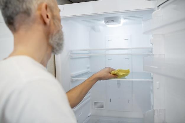 Robię sprzątanie. siwowłosy mężczyzna czyści lodówkę w kuchni