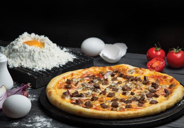 Robienie ciasta na pizzę i gotowa cała pizza