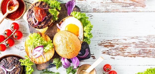 Robienie domowego burgera. składniki do gotowania na drewnianym stole. widok z góry lub leżał płasko. skopiuj miejsce