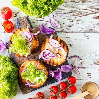 Robienie domowego burgera. składniki do gotowania na drewnianym stole. widok z góry.