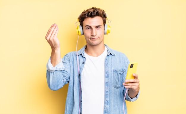 Robienie gestu kaprysu lub pieniędzy, każącego spłacić długi!. koncepcja słuchawek i smartfona