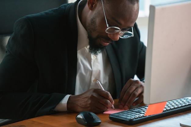 Robienie notatek. afro-przedsiębiorca, biznesmen pracujący skoncentrowany w biurze. wygląda serio i zajęty, ma na sobie klasyczny garnitur, marynarkę.