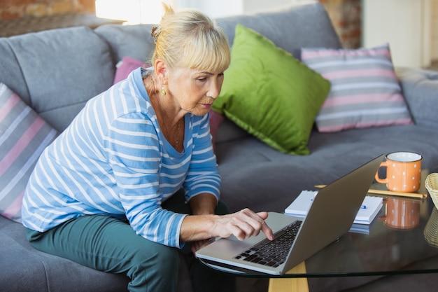 Robienie notatek podczas lekcji. starsza kobieta uczy się w domu, pobiera kursy online