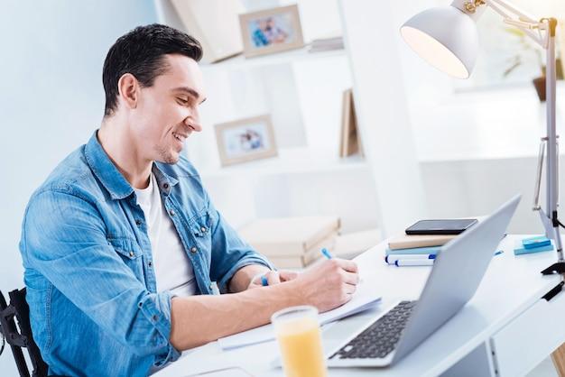 Robienie notatek. radosny młody człowiek z uśmiechem na twarzy i pochyloną głową siedząc w półpozycji