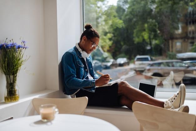 Robienie notatek. uważny międzynarodowy mężczyzna siedzący w pół pozycji i robiący notatki