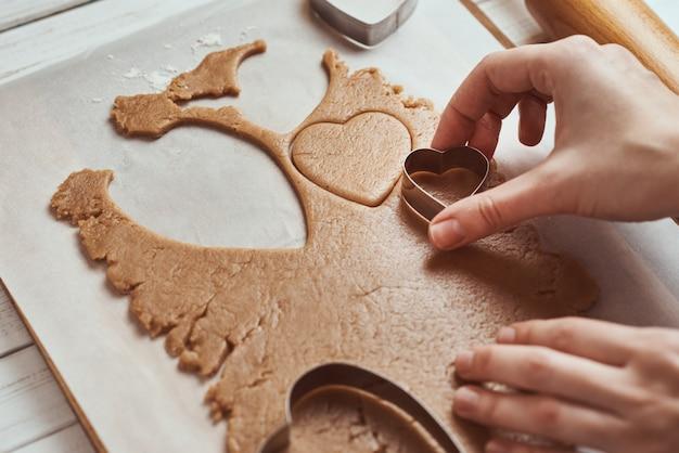 Robienie piernikowych ciasteczek w kształcie serca na walentynki. kobiety ręka używać foremki do ciastek. koncepcja żywności na wakacje