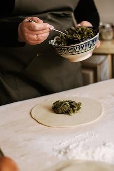Robienie pierogów, manti i chinkali z mielonej wołowiny, jagnięciny i ciasta. domowe jedzenie