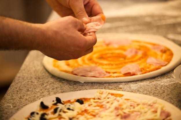 Robienie pizzy w restauracji, zbliżenie rąk szefa kuchni?