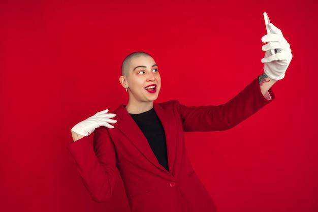 Robienie selfie lub vloga. portret młodej kobiety kaukaski łysy na białym tle na czerwonej ścianie.