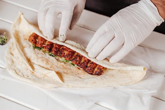 Robienie shawarma z mięsem kebab i chlebem arabskim.