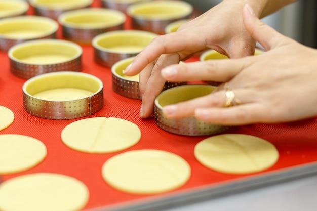 Robienie słodkich lub pikantnych tart i quiche. narodowa francuska kuchnia domowa. wykonany ręcznie. trening gotowania kucharz wypełnia naczynie do pieczenia nadzieniem.