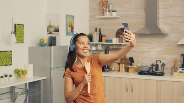 Robienie sobie selfie i śpiewanie rano przy użyciu drewnianej łyżki. energiczna, pozytywna, szczęśliwa, zabawna i urocza gospodyni tańcząca samotnie w domu. rozrywka i wypoczynek samemu w domu