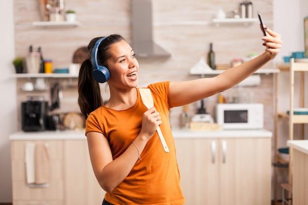 Robienie sobie selfie i śpiewanie rano przy użyciu drewnianej łyżki