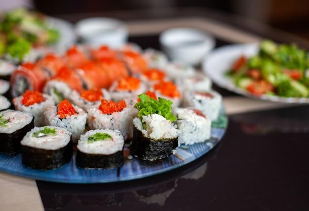 Robienie sushi i bułek w domu. sushi z owocami morza, sałatką i białym ryżem. jedzenie dla rodziny i przyjaciół. zestaw różnych rolek i sushi na tacy.