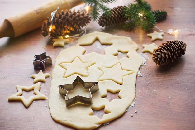 Robienie świątecznych ciasteczek na drewnianym stole z różnymi dodatkami, przygotowanie do świąt bożego narodzenia i nowego roku