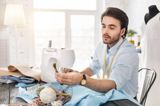 Robienie ubrań. zdeterminowany ciemnowłosy krawiec uśmiechnięty i pracujący na maszynie do szycia