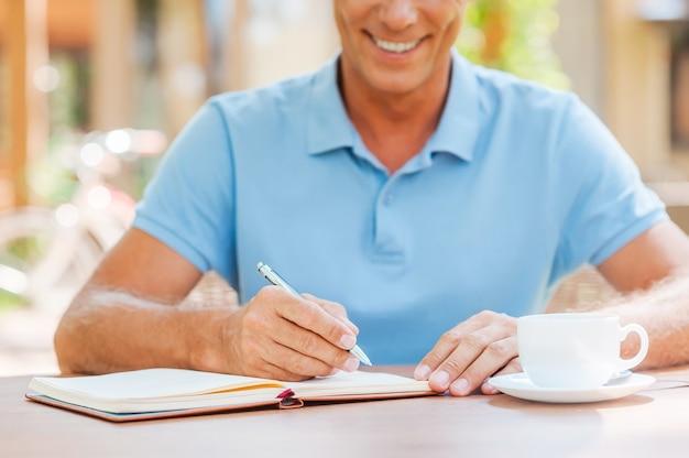 Robienie ważnych notatek. zbliżenie: pewny siebie dojrzały mężczyzna pisze coś w swoim notesie i uśmiecha się siedząc przy stole na zewnątrz z domem w tle