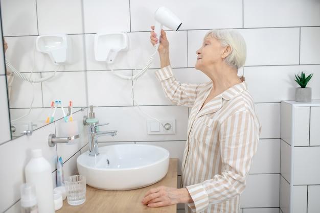 Robienie włosów. siwa starsza kobieta suszy włosy w łazience