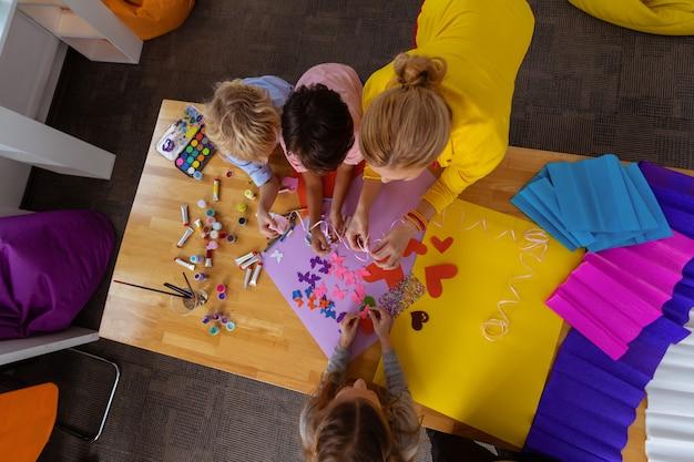 Robienie wycinanek. widok z góry na blond nauczycielkę i uczniów używających kolorowego papieru do robienia wycinanek