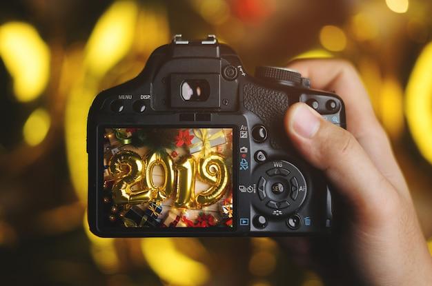 Robienie zdjęć aparatem. 2019 golden balloon between christmas decoration