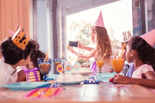Robienie zdjęć. długowłosa ostrożna dziewczyna stojąca z nowoczesnym smartfonem i robiąca selfie z przyjaciółmi na imprezie