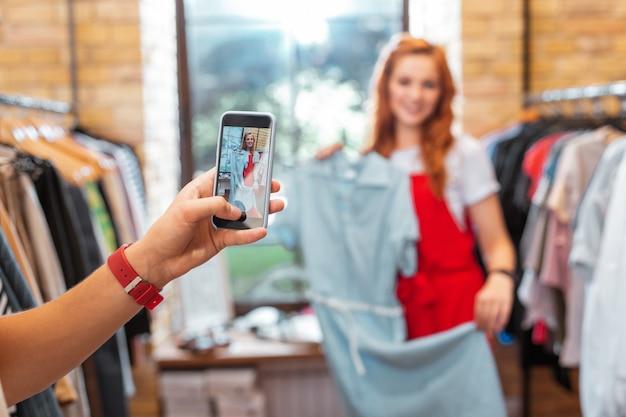 Robienie zdjęć. piękna młoda dziewczyna pozuje z śliczną sukienką w sklepie z ubraniami, a miły chłopak robi jej zdjęcia