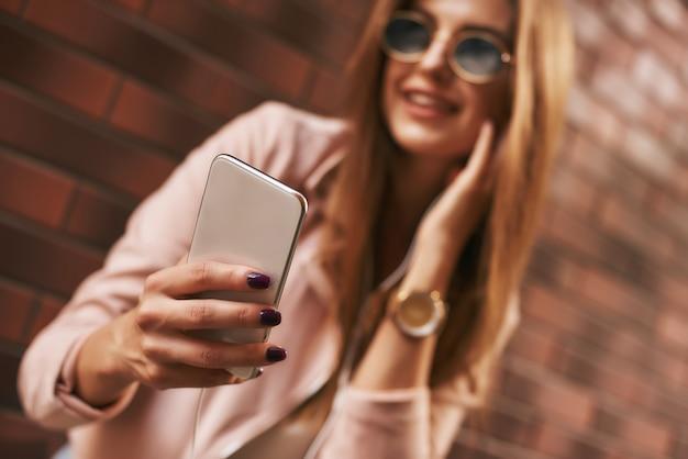 Robienie zdjęć piękna stylowo ubrana dziewczyna pozuje na tle cegły