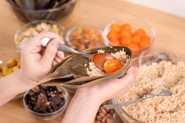 Robienie zongzi - składnik chińskich klusek ryżowych zongzi na stole w domu na obchody dragon boat festival, zbliżenie, styl życia.