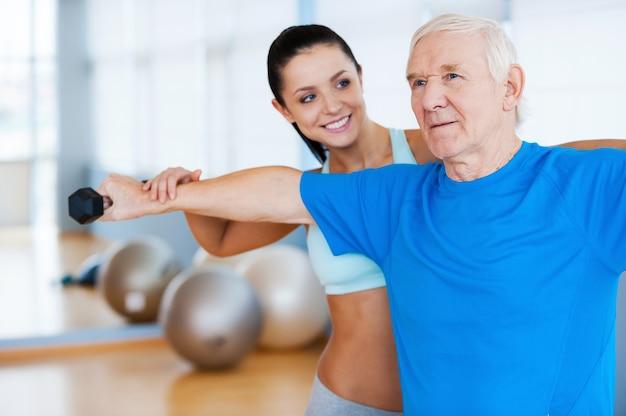 Robisz postępy! pewna siebie fizjoterapeutka pracująca ze starszym mężczyzną w klubie fitness
