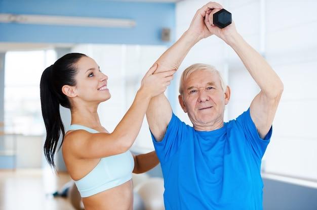Robisz wielkie postępy! pewna siebie fizjoterapeutka pracująca ze starszym mężczyzną w klubie fitness