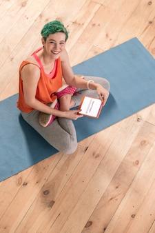 Roboczy e-mail. rozpromieniona kobieta sprawdzająca swoją roboczą pocztę e-mail na małym tablecie siedzącym na macie sportowej