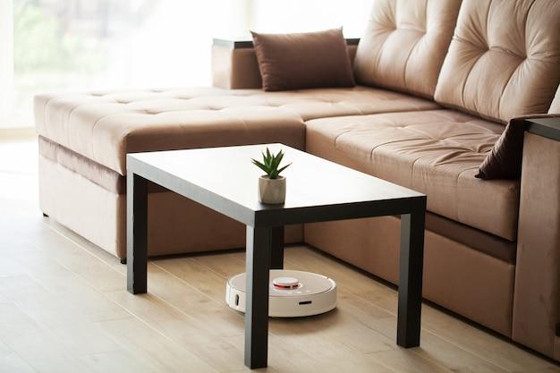 Robot odkurzający działa na drewnianej podłodze w salonie.