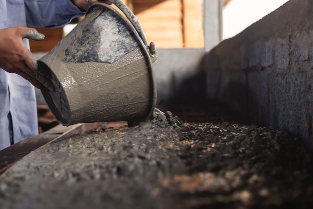 Robotnicy budowlani robią cement w pracach remontowych domu.