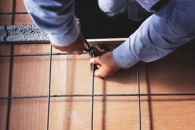 Robotnicy budowlani wiążąc stal żelbetową.