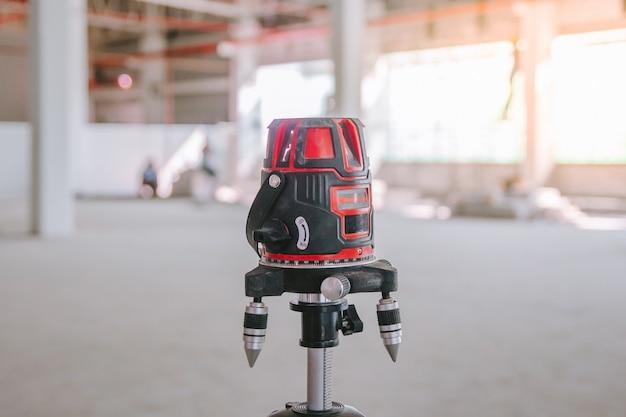 Robotnicy budowlani wykonują pomiary za pomocą narzędzia do pomiaru poziomu lasera w niszy dla grzejników
