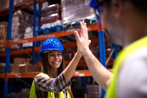 Robotnicy przemysłowi dotykają się i klaszczą za udaną pracę